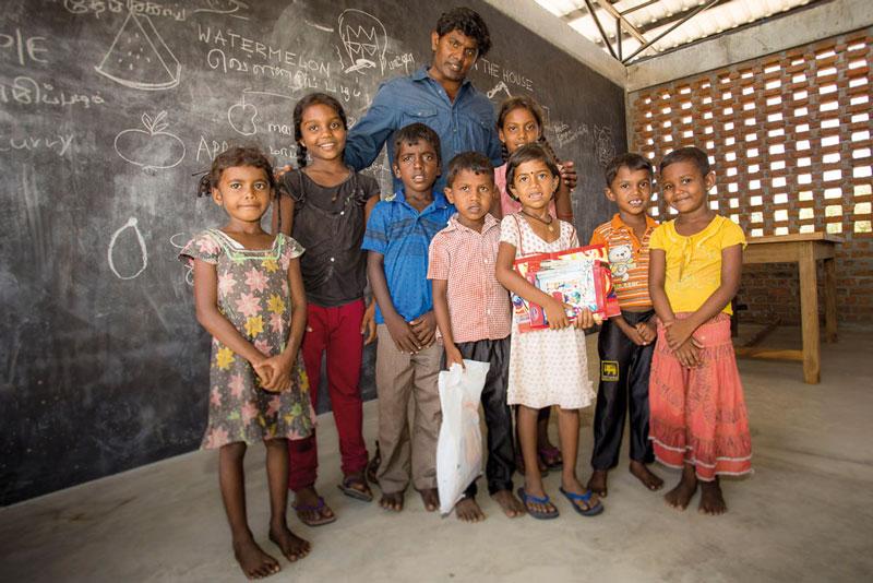 Der Schulgründer Vincen Francis Jesudasan, gemeinsam mit Schülerinnen und Schülern in den Räumen des neu errichteten Lanka Learning Centers.Foto: ©Lichtbildarena